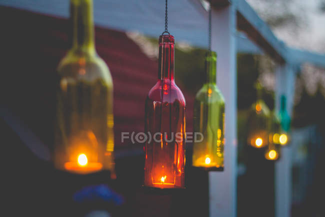 Colorful glass bottles with burning candles — Stock Photo