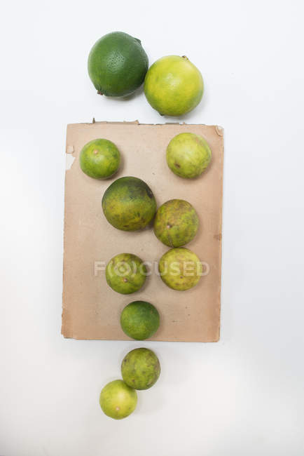 Limes with paper on white surface — Stock Photo