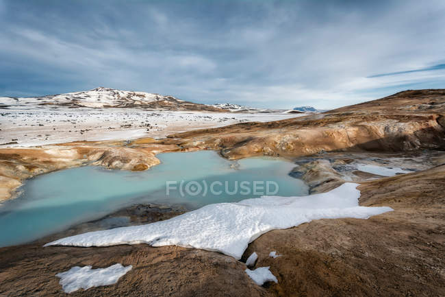 Snowy land and frozen lake — Stock Photo