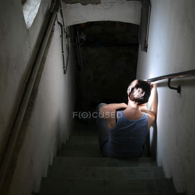 Вернуться мнение печальный человек, сидящий на лестницы в доме — стоковое фото