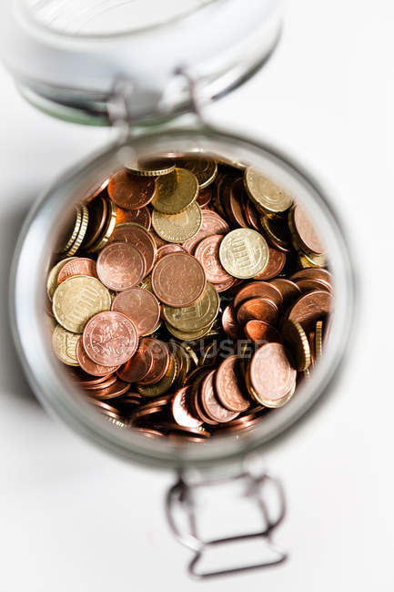 Top view of coins heap in opened preserving jar — Stock Photo