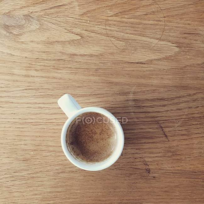 Espresso cup of coffee on wooden table — Stock Photo