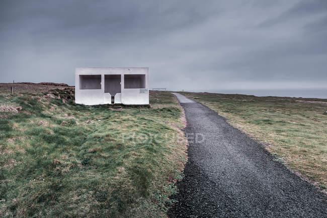 Route asphaltée avec cabine blanche bus stop sur le bord de la route — Photo de stock