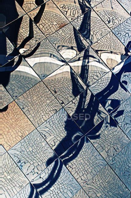 Vista diurna de pedras do pavimento e sombras refletidas no espelho quadrado telhas — Fotografia de Stock