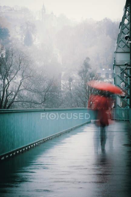 Frau mit Regenschirm zu Fuß am Steg, Bewegungsunschärfe — Stockfoto