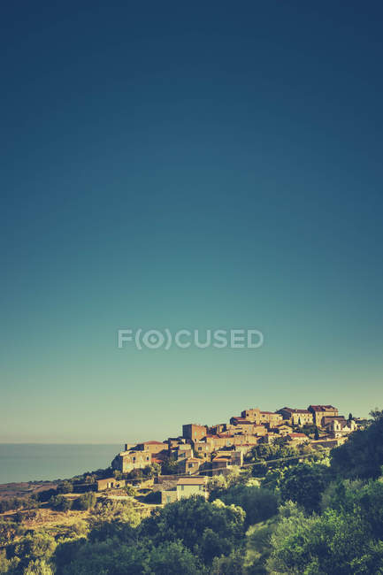 Seaside landscape with mountain village in sunlight, Corsica France — Stock Photo