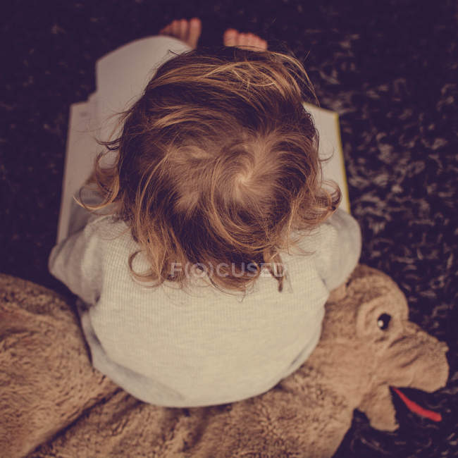 Overhead of toddler sitting wit book — Stock Photo