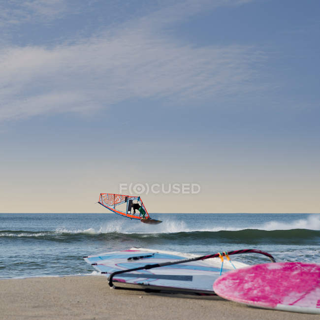 Freestyle sport, windsurfer man jumping with surf boat in ocean water — Stock Photo