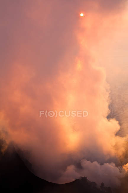Colorful orange lightened clouds over mountains at sunset — Stock Photo