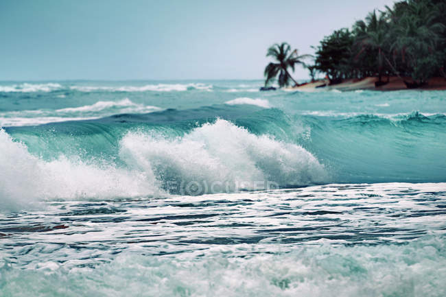 Wave breaking on tropical beach — Stock Photo