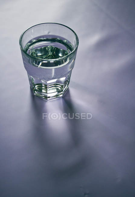 Copo de água na superfície branca — Fotografia de Stock