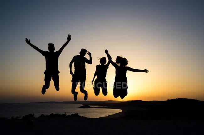 Sonnenuntergang und glückliche Menschen Silhouetten springen — Stockfoto