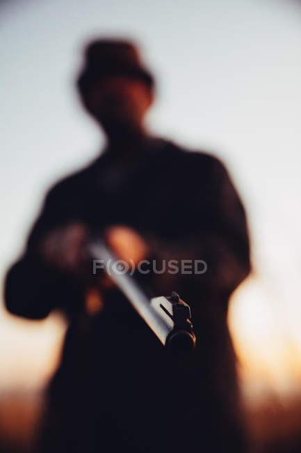Сосредоточиться на огнестрельное оружие дальновидность и охотник на фоне — стоковое фото