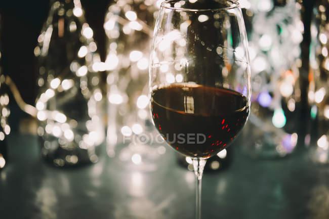 Glas Rotwein und Lichter im Hintergrund — Stockfoto