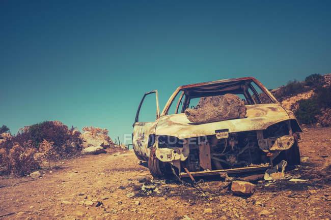 Roto auto oxidada con piedra en la capilla en terreno desértico - foto de stock