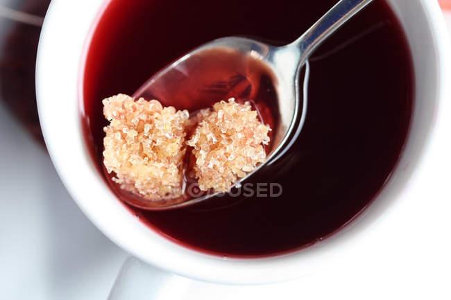 Cubos de açúcar mascavo em chá de frutas — Fotografia de Stock