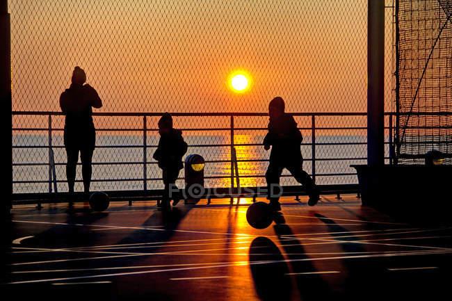 Siluetta della madre con due bambini sul molo, bambini che giocano con la sfera — Foto stock