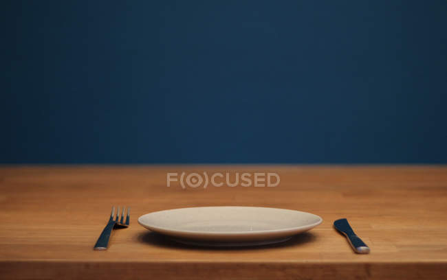 Wooden table with white plate, fork and knife — Stock Photo