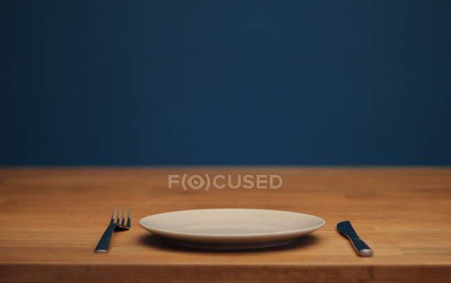 Holztisch mit weißen Teller, Messer und Gabel — Stockfoto