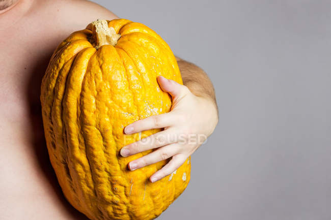 Big yellow pumpkin in human hand — Stock Photo