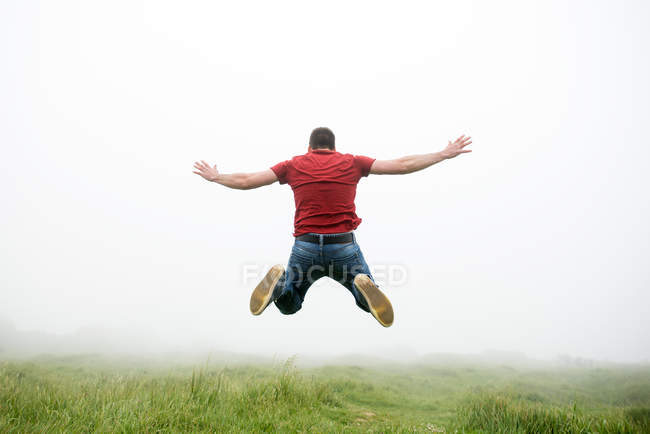 Rear view of man jumping in field — Stock Photo