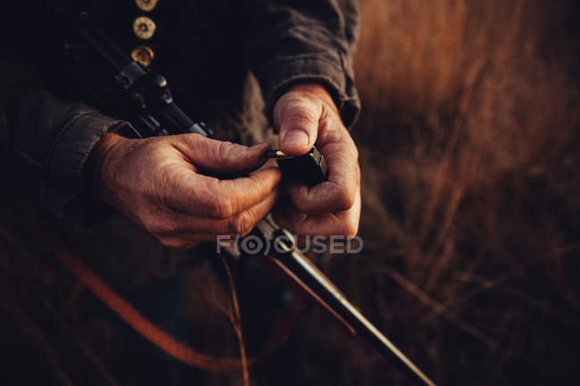 Close-up view of hunter hands holding firegun and bullet — Stock Photo