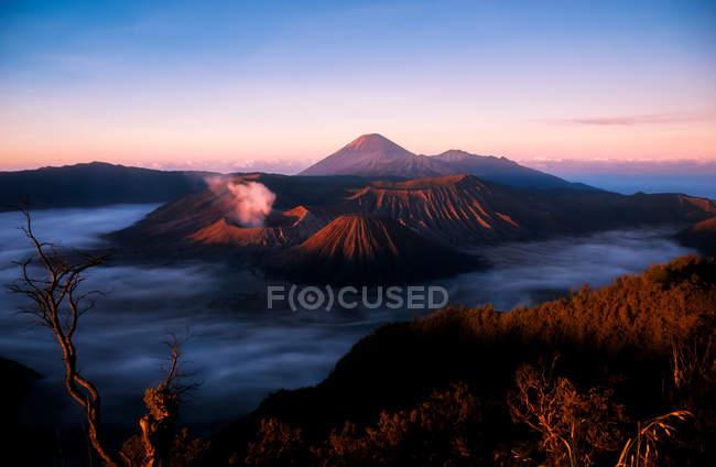 Vulcão Monte Bromo e o lago Batur, roxo céu do sol, Parque Nacional de Bromo Tengger Semeru, regência Bangli, Bali, Indonésia — Fotografia de Stock