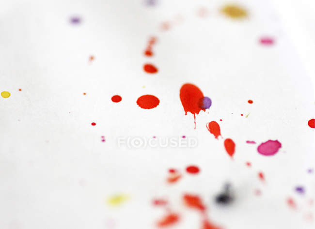 Colorful paint splashes on white paper surface — Stock Photo