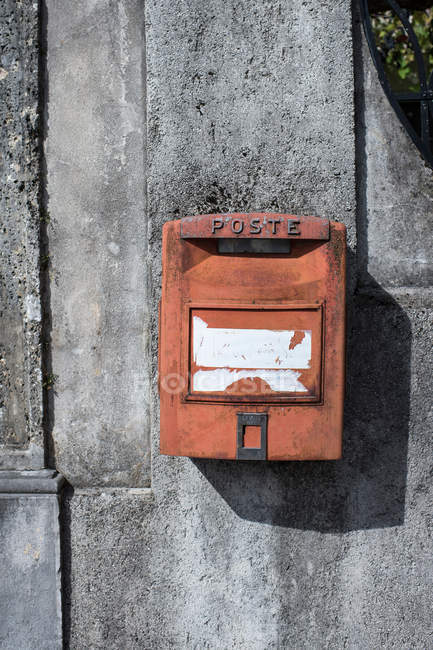 Red post mailbox on cement building wall — container, traditional