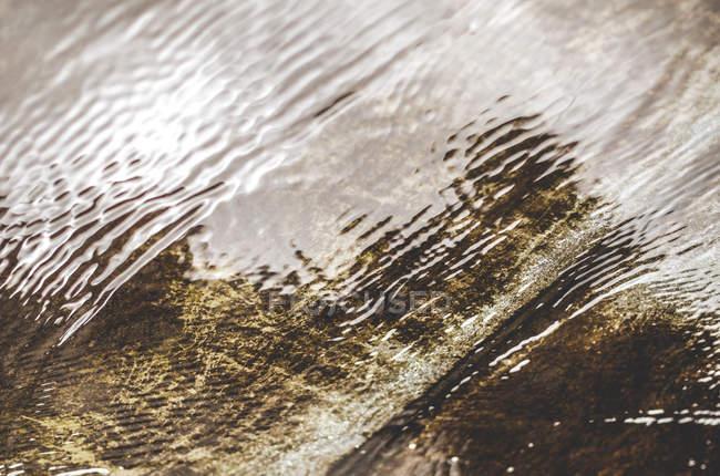 Flaque d'eau avec la réflexion sur la surface de l'eau ondulées — Photo de stock