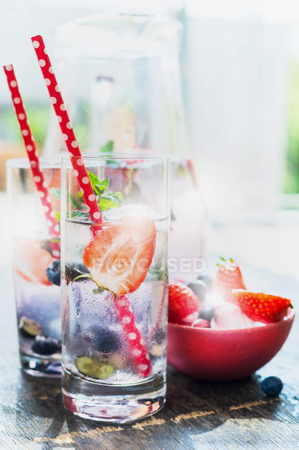 Daytime view of fruit drinks with halved strawberries and drinking straws — Stock Photo