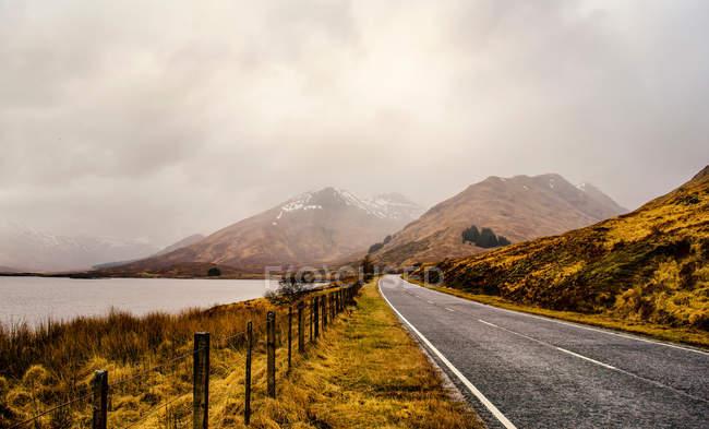 Route route goudronnée de montagne, le lac au bord de la route droite, brûlé l'herbe des collines — Photo de stock