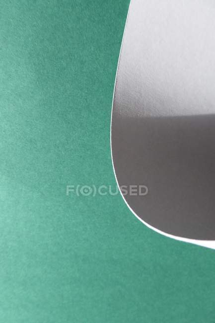 Closeup view of bent white paper on green background — Stock Photo