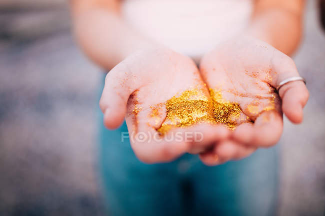 Close-up view of hands holding golden glitter — Stock Photo