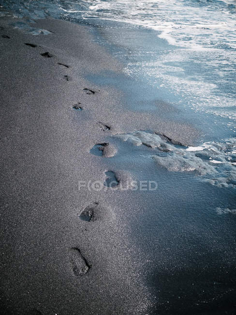 Wet sand beach with footprints — Stock Photo