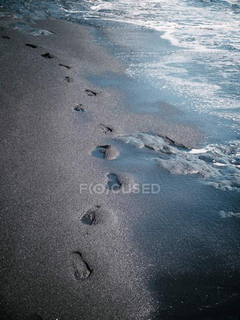 Plage de sable humide avec empreintes — Photo de stock