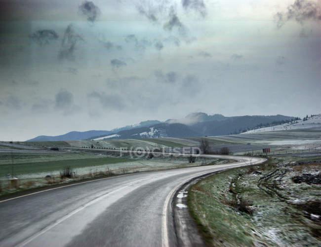 Route de route goudronnée courbe aux montagnes en hiver — Photo de stock
