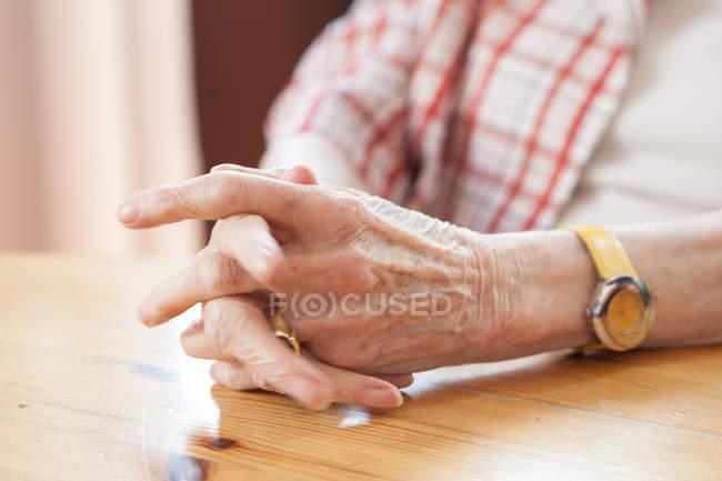 Mains ridées de vieille femme à table en bois — Photo de stock