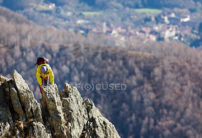 Traveler person climbing on rocky mountain top — Stock Photo