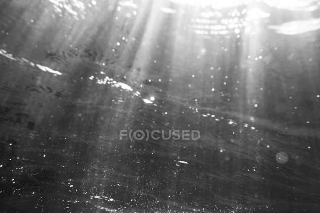 Abstrakte Struktur der Unterwasser mit Sonnenstrahlen und Luftblasen — Stockfoto