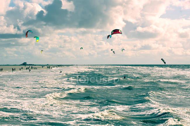 Kite surf sur la côte de la mer par temps venteux sous un ciel lourd de nuages — Photo de stock