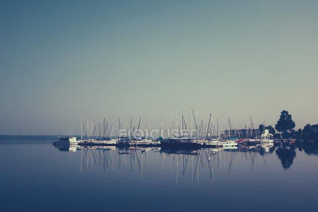 Вітрильники, розмірковуючи про спокійне озеро води у заході сонця світлі — стокове фото