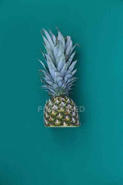 Half of pineapple on blue — Stock Photo