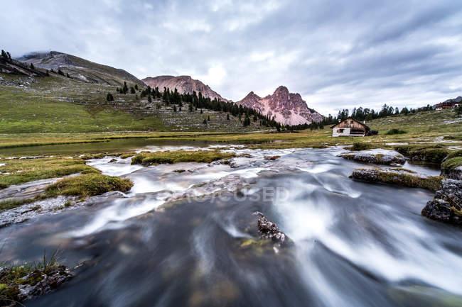 Lago di montagna circondato da montagne e colline — Foto stock