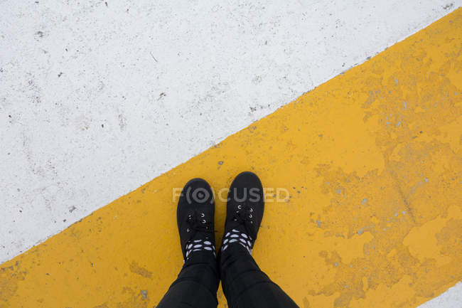 Male feet in black sneakers on yellow white surface — Stock Photo