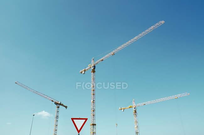 Vista diurna de três guindastes de construção com sinal de estrada — Fotografia de Stock