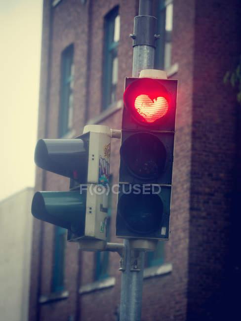 Ampel mit leuchtenden roten Herzschild — Stockfoto