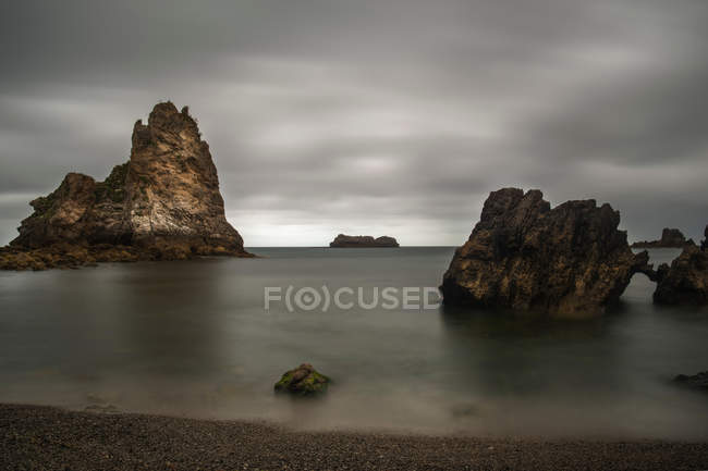 Distant view of rocks on ocean coast under cloudy sky — Stock Photo