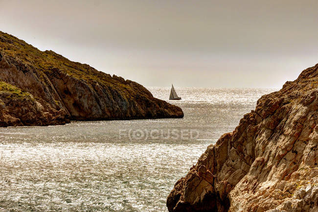 Sailboat by the rocky coastline — Stock Photo