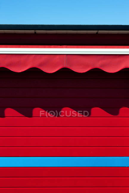 Red wall with striped awnings curves and shadow — Stock Photo